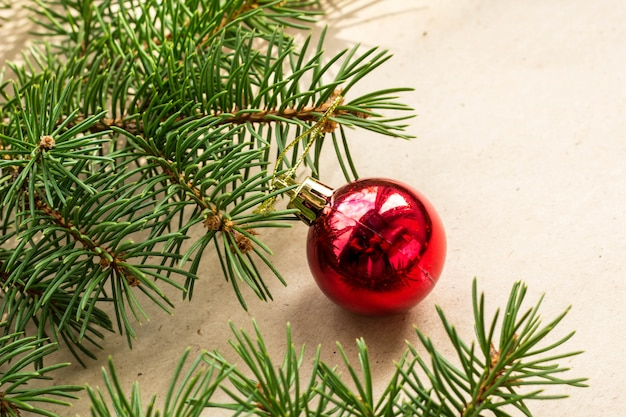 Galhos de árvore do abeto decorados com bolas vermelhas de natal como fronteira em um feriado rústico