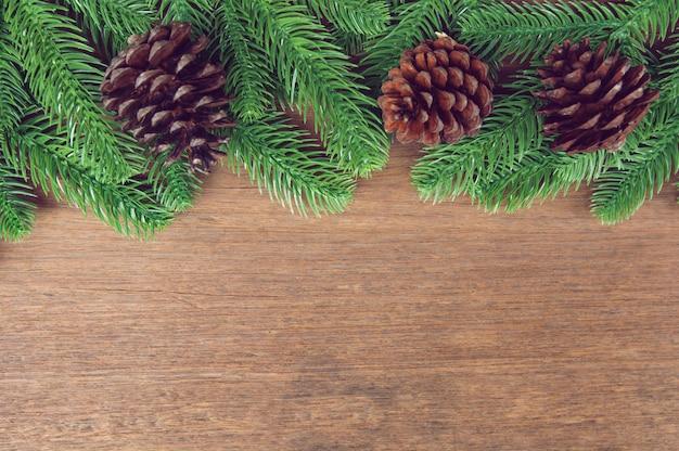 Galhos de árvore do abeto e pinhas com decoração em uma placa de madeira
