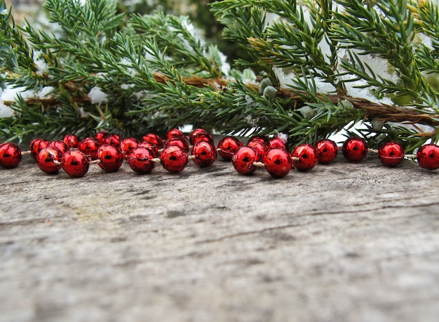Galhos de árvores coníferas com neve e contas vermelhas em um espaço de fundo de madeira rústica para texto de cópia