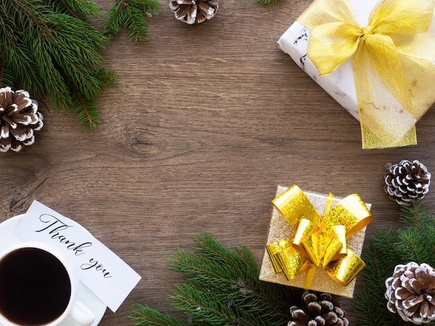 Galhos de árvores de natal com cones de pinheiro e caixa de presente