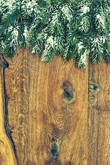 Galhos de árvores de natal com neve em fundo de madeira. foto em tons vintage