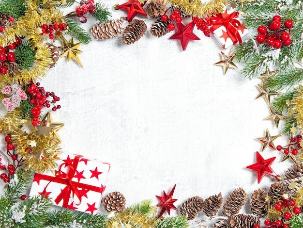 Galhos de árvores de natal com presentes, estrelas, decoração vermelha em fundo branco. conceito de férias de inverno