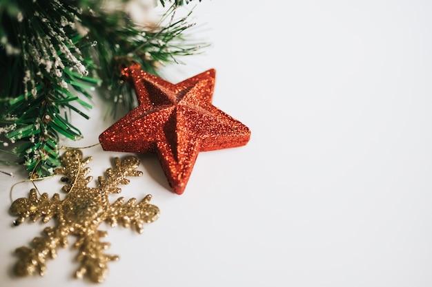 Galhos de árvores de natal decoradas com brinquedos estrela vermelha, floco de neve