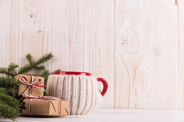 Galhos de árvores de natal, presentes e bebida quente em uma caneca, natal, cartão de felicitações. copyspace.