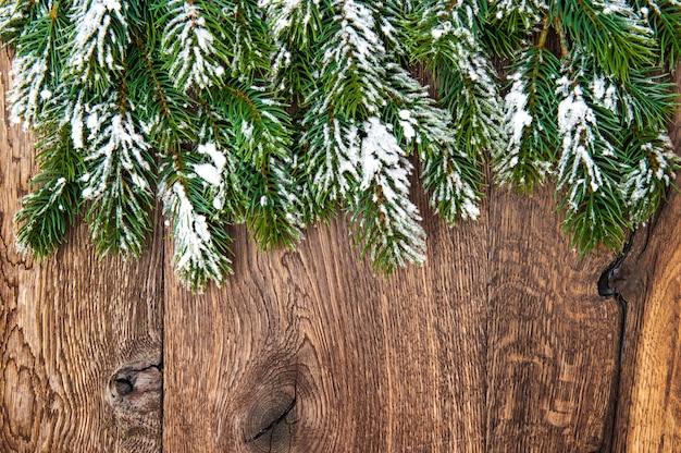 Galhos de árvores de natal sobre fundo de madeira. borda verde de galhos perenes não decorados