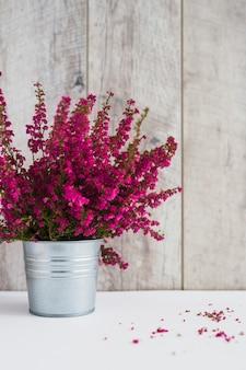 Galhos de floração rosa no recipiente de alumínio na mesa branca contra a prancha