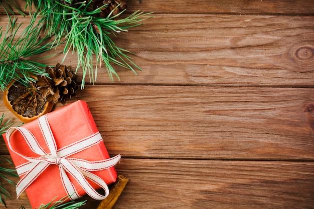 Galhos de natal e caixa vermelha na mesa de madeira
