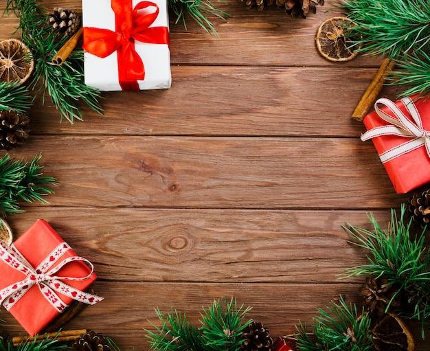 Galhos de natal e caixas na placa de madeira