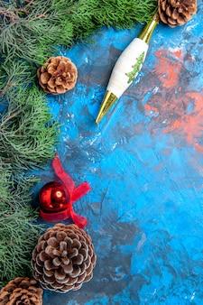 Galhos de pinheiro com pinhas na superfície azul-avermelhada de vista superior