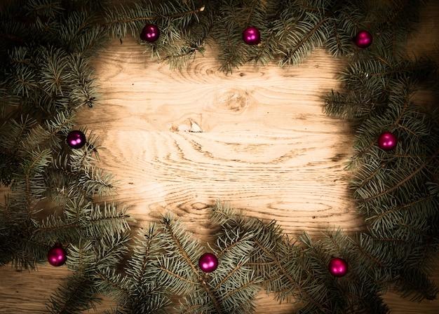 Galhos de pinheiro verde no chão de madeira com escurecimento nas bordas com bolas de natal