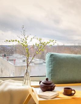 Galhos de primavera na garrafa na mesa com uma manta, travesseiro, livro, bule e uma xícara com uma cidade chuvosa do lado de fora