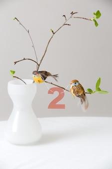 Galhos de uma árvore em um lindo vaso branco com pássaros e o número 2 como decoração