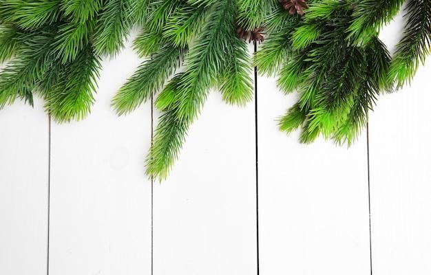 Galhos e cones de pinheiro em fundo claro de madeira