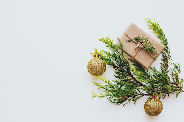 Galhos verdes brilhantes de pinheiro e uma caixa de presente marrom clara e bolas douradas
