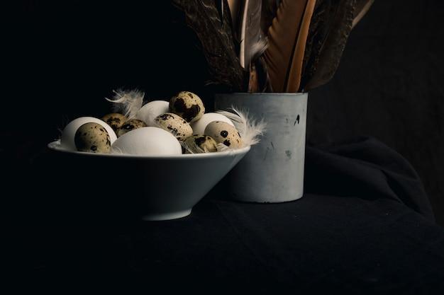 Galinha e codorna ovos entre penas na tigela perto de grandes penas na lata velha