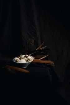 Galinha e codorna ovos entre penas na tigela perto de grandes penas