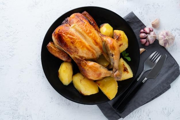 Galinha inteira grelhada na placa na tabela branca, carne cozida com batatas. vista de cima, copie o espaço