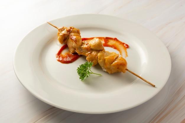 Galinha no no espeto de bambu dos espetos na placa branca, fundo brilhante de mármore. dieta de alimentos com pouca gordura.