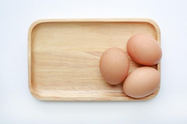 Galinha três ovos na bandeja de madeira isolada no fundo branco.