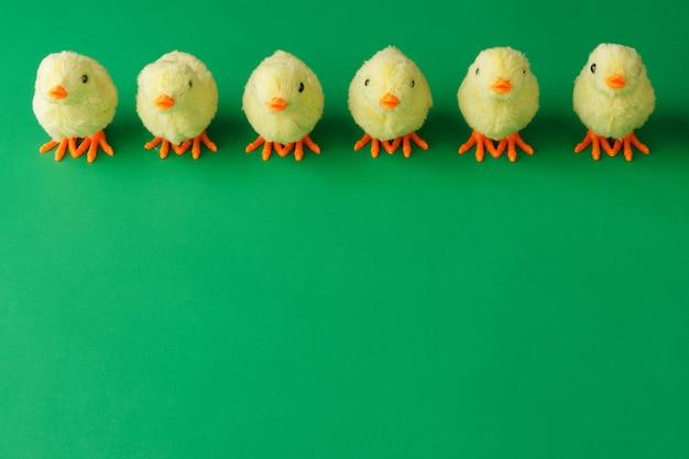 Galinhas de brinquedo amarelas estão em uma fileira sobre um fundo verde.