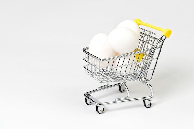 Galinhas ovos brancos que estão em um carrinho de compras.