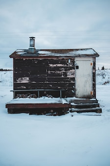 Galpão marrom e branco coberto de neve