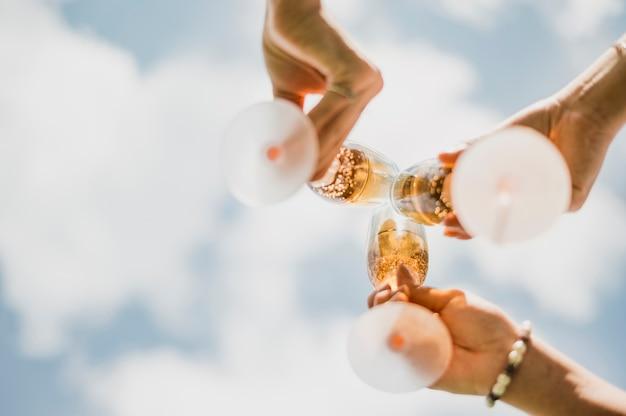 Galsses de baixo ângulo com champanhe e nuvens vista