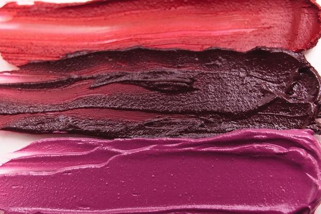 Gama de cosméticos coloridos manchados de batom. publicidade criativa, fundo comercial. revista glamorosa, conceito de beleza