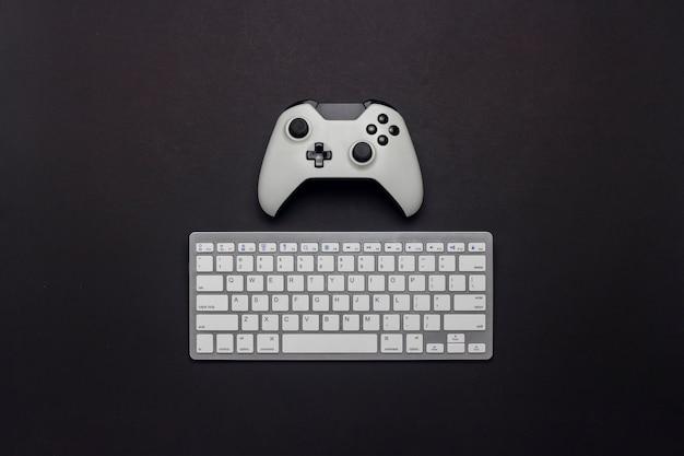Gamepad branco e teclado em um fundo preto. táticas do jogo. jogo de conceito no console e pc, jogos de computador. vista plana leiga, superior.
