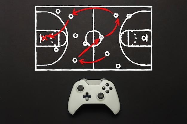 Gamepad branco sobre um fundo preto. adicionado um esquema de campo de basquete. táticas do jogo. jogo do conceito de basquete no console, jogos de computador. vista plana leiga, superior.