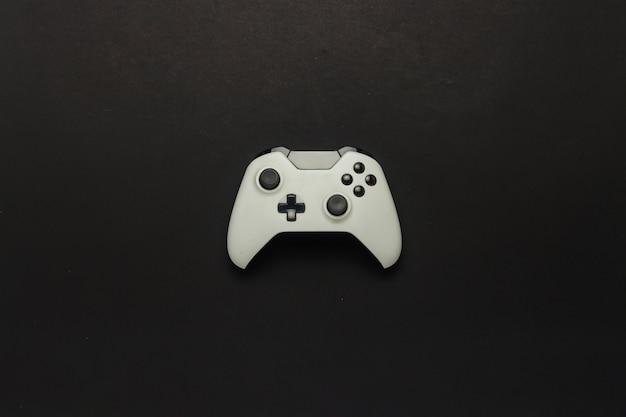 Gamepad branco sobre um fundo preto. jogo de conceito no console, jogos de computador. vista plana leiga, superior.