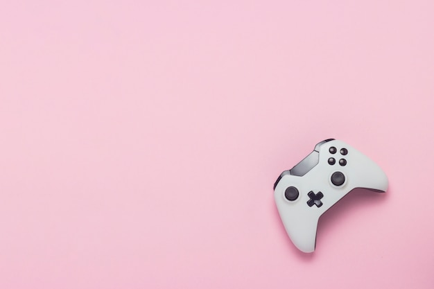 Gamepad branco sobre um fundo rosa. jogo de conceito no console, jogos de computador. vista plana leiga, superior.