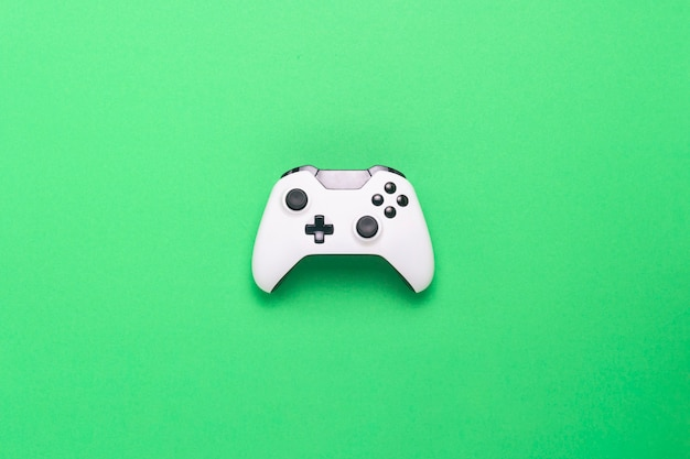 Gamepad branco sobre um fundo verde. jogo de conceito no console, jogos de computador. vista plana leiga, superior.