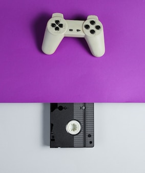 Gamepad, cassete de vídeo em uma mesa cinza roxa. estilo retro dos anos 80. vista do topo