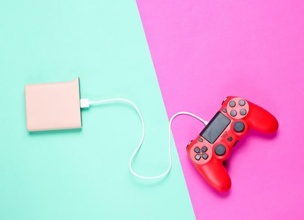 Gamepad de plástico vermelho moderno está cobrando do banco do poder em fundo de néon colorido.
