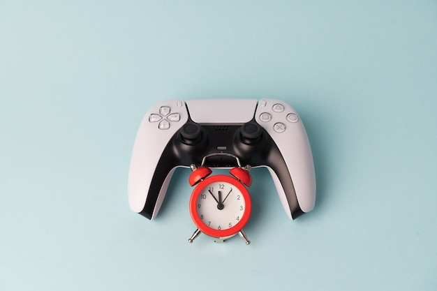 Gamepad do console de videogame na parede azul com despertador vermelho. tim para jogar. problema do jogador na dependência do jogo.