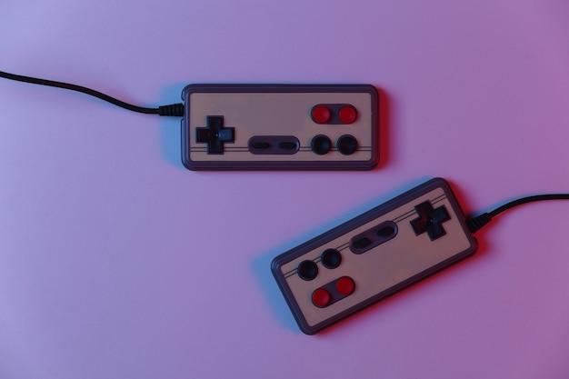 Gamepad retro em luz de néon gradiente vermelho azul. jogos, competição de videogame. vista do topo