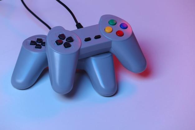 Gamepad retro em luz de néon gradiente vermelho azul. jogos, competição de videogame.