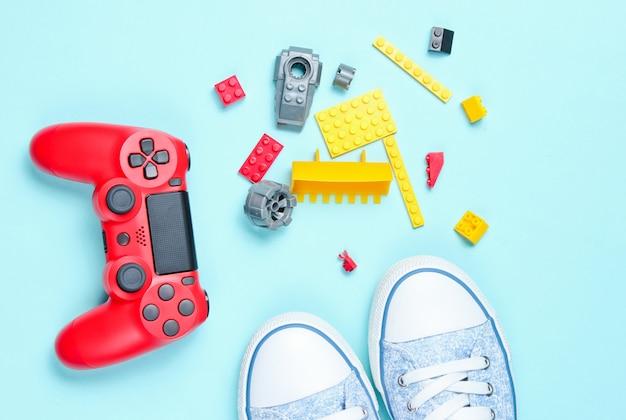 Gamepad vermelho, tijolos de construtor infantil, tênis, vista superior