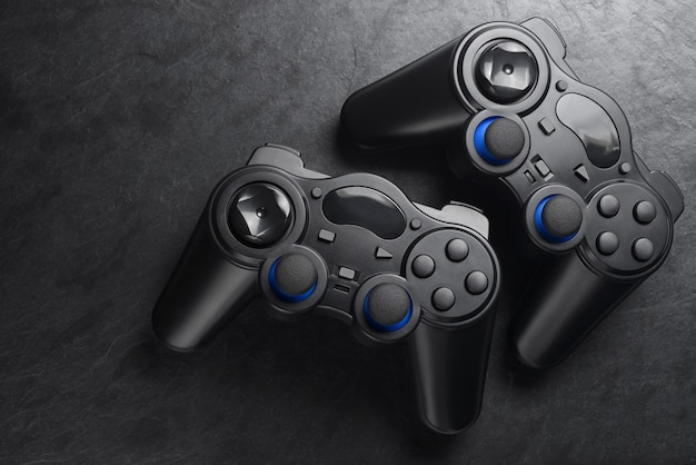 Gamepads. dois joysticks de plástico sem fio em fundo de ardósia preta. copie o espaço