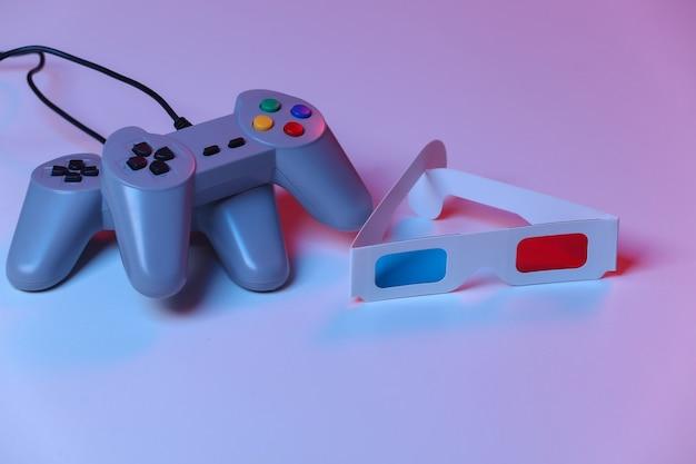 Gamepads retrô com óculos 3d em luz de néon azul vermelha. atributos anos 80