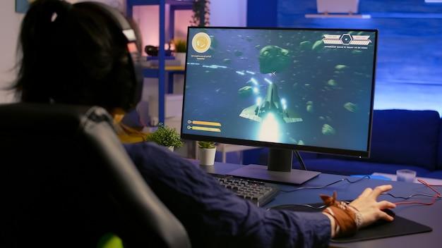 Gamer vencedor profissional que vence competição de tiro espacial usando equipamento rgb profissional