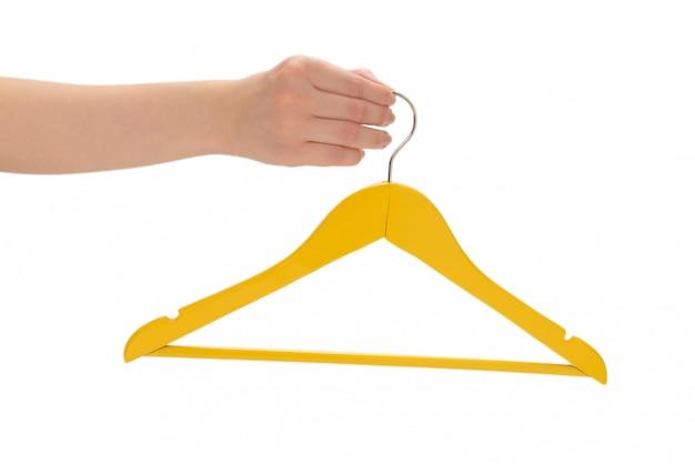 Gancho amarelo na mão da mulher isolado no branco.