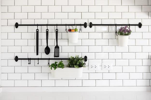 Gancho de utensílio de cozinha na parede de tijolo branco