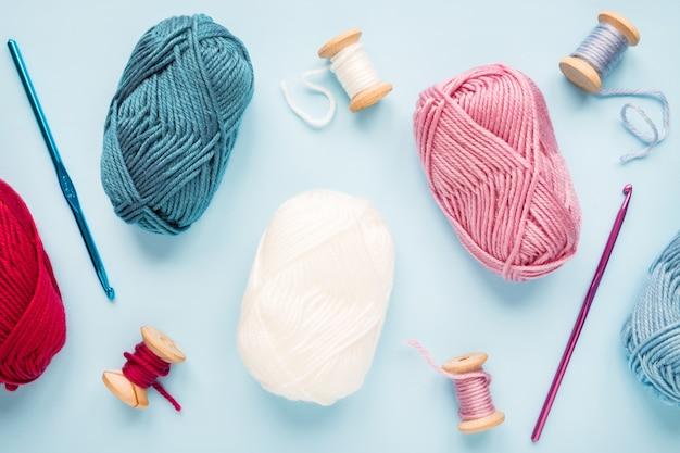 Ganchos de crochê multicoloridos com novelos de lã em um fundo azul