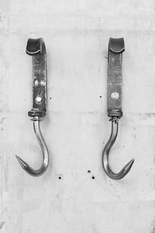 Ganchos de metal vintage para feno ou carne anexado a uma parede de concreto