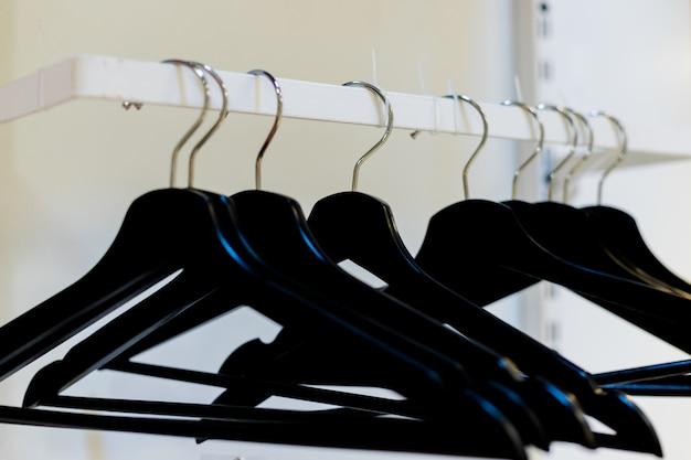 Ganchos de roupa de madeira vazios no vestiário vazio.