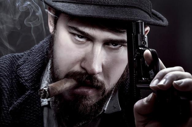 Gângster barbudo de chapéu com uma arma na mão e um cigarro na boca na parede preta