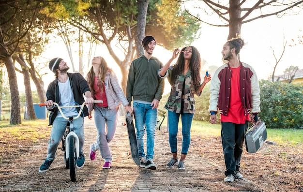 Gangue de amigos urbanos caminhando no skatepark da cidade com a luz do pôr do sol