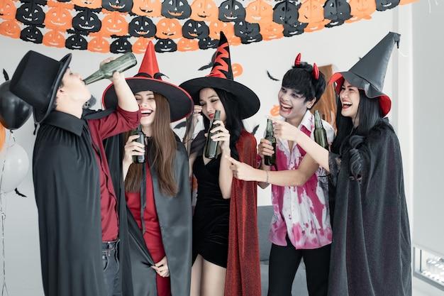 Gangue de jovem asiático fantasiado de bruxa, feiticeiro e festa de halloween para dançar e beber e bêbado no quarto. grupo adolescente tailandês com celebrar o halloween. festa de halloween do conceito em casa.